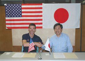 事前キャンプの合意書を締結した金丸謙一市長(右)と米国トライアスロンチームのジョン・ファラー氏=館山市役所で