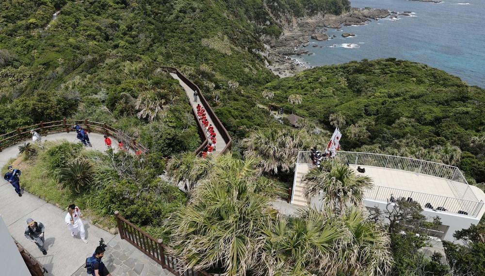 鹿児島県南大隅町の佐多岬でトーチを掲げ聖火を運ぶランナー=27日午後