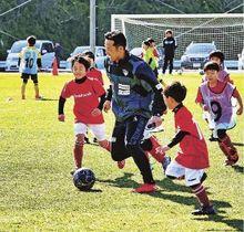 サッカー教室で横浜FCのコーチと触れ合う子どもら(18日、和歌山県上富田町朝来の上富田スポーツセンターで)