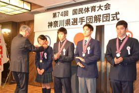 記念のメダルを授与される水泳の選手=横浜市内のホテル