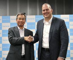 記者会見で握手するクラレの伊藤正明社長(左)と米カルゴンカーボン社のランダール・ダース社長=20日午後、東京都千代田区