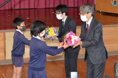 児童から花束を受け取る羽生善治九段(右)と豊島将之竜王=指宿市の今和泉小学校