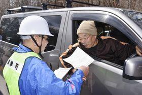 注意を呼び掛けるチラシを受け取る通行者(右)=19日午前、群馬県草津町