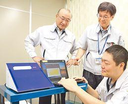展示会に向けてデモ機を操作する担当社員と多田社長(左)=北陸電気工業