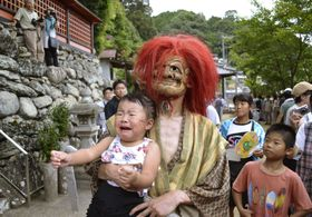 椎出厳島神社の奇祭「椎出鬼の舞」で、鬼に抱き上げられ泣き叫ぶ子ども=16日午後、和歌山県九度山町