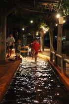 明かりがともった足湯で遊ぶ子どもたち=雲仙市小浜町