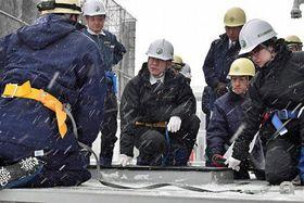 原燃社員(左)の説明を受けながら配管ピットを確認する規制委の山中委員(中央)=18日午後、六ケ所村