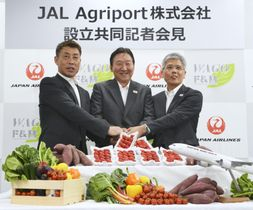新会社「JALアグリポート」設立を発表し、記者会見で手を取り合う日本航空の藤田直志副社長(右)ら=21日午後、成田空港