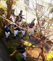 みんなで協力して白いホースを持ち、消火活動に取り組む沖縄工業高校の野球部員ら(提供)