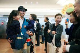 約1年4カ月ぶりに帰国し、家族に迎えられ笑顔の57次越冬隊の藤原宏章隊員(左)=23日午後、東京・羽田空港