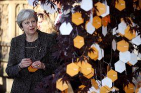 大聖堂前の「希望の木々」にメッセージをくくりつけるメイ首相=22日、マンチェスター(ゲッティ=共同)