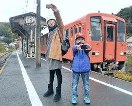 列車をバックにデジタルカメラで自分を撮影するする子どもたち