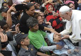 ブラジル・リオデジャネイロのスラム街で、子どもを祝福するローマ教皇フランシスコ=2013年7月(AP=共同)