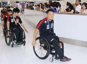 金メダルを胸に帰国した池透暢選手(手前)ら車いすラグビー日本代表(11日午後、成田空港)