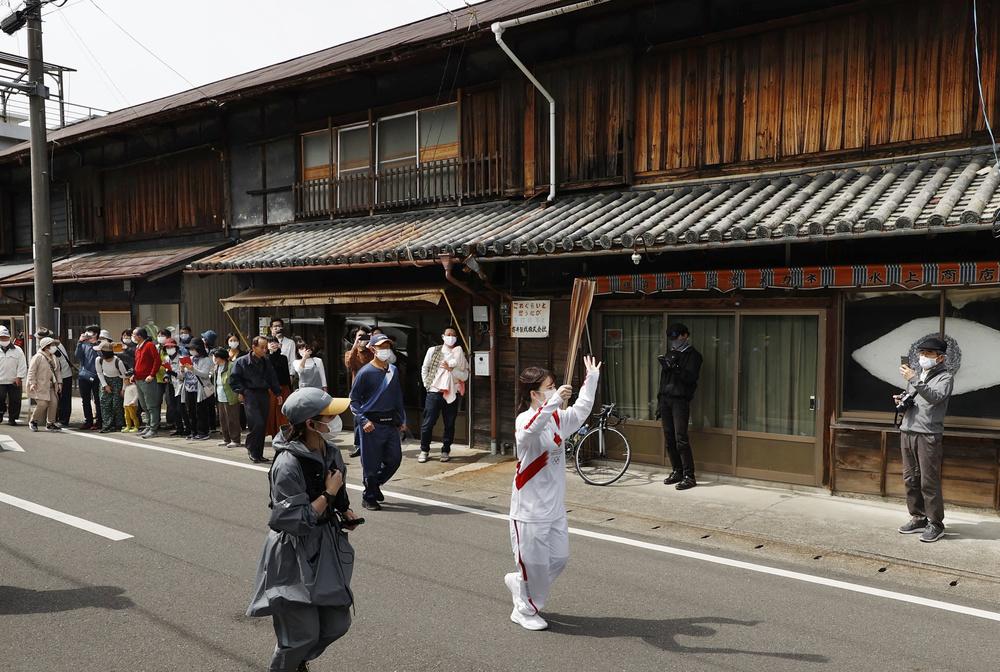 昭和時代前半の町並みが残る徳島県神山町を走る聖火ランナー=15日午後