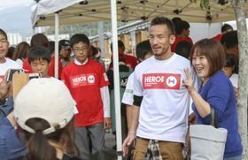 広島県坂町の仮設住宅を訪ね、被災者らと記念撮影する中田英寿さん(右から2人目)=18日午後