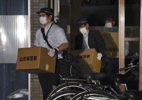加藤紘貴容疑者の自宅マンションから押収物を運び出す山形県警の捜査員ら=12日夜、山形市