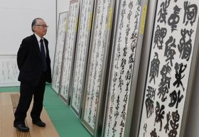 応募作品を審査する中央審査員の石飛博光さん=長崎市、県美術館