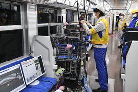 JR八高線の列車内で通信状況を確認する関係者=28日未明
