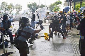 立法会の敷地に突入し、警官隊(左側)と衝突する若者ら=12日、香港(共同)