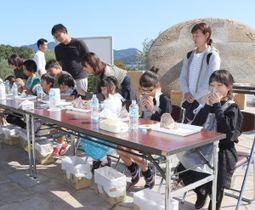 「オリーブとんバーガー」の早食いに挑戦する子どもたち=小豆島町西村、小豆島オリーブ公園