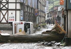 豪雨の被害を受けた大分県日田市の天ケ瀬温泉で横倒しになった木や車=8日午前8時46分