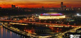 大規模な改修工事を終え、サッカー専用スタジアムに生まれ変わったルジニキ競技場。屋根がロシア国旗の色にライトアップされ、夕暮れに浮かび上がった。開幕戦のほか、準決勝と決勝など7試合が行われる=2017年11月8日(共同)