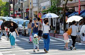 今年初の真夏日を観測し、日傘を差した歩行者が目立った=山形市中心街