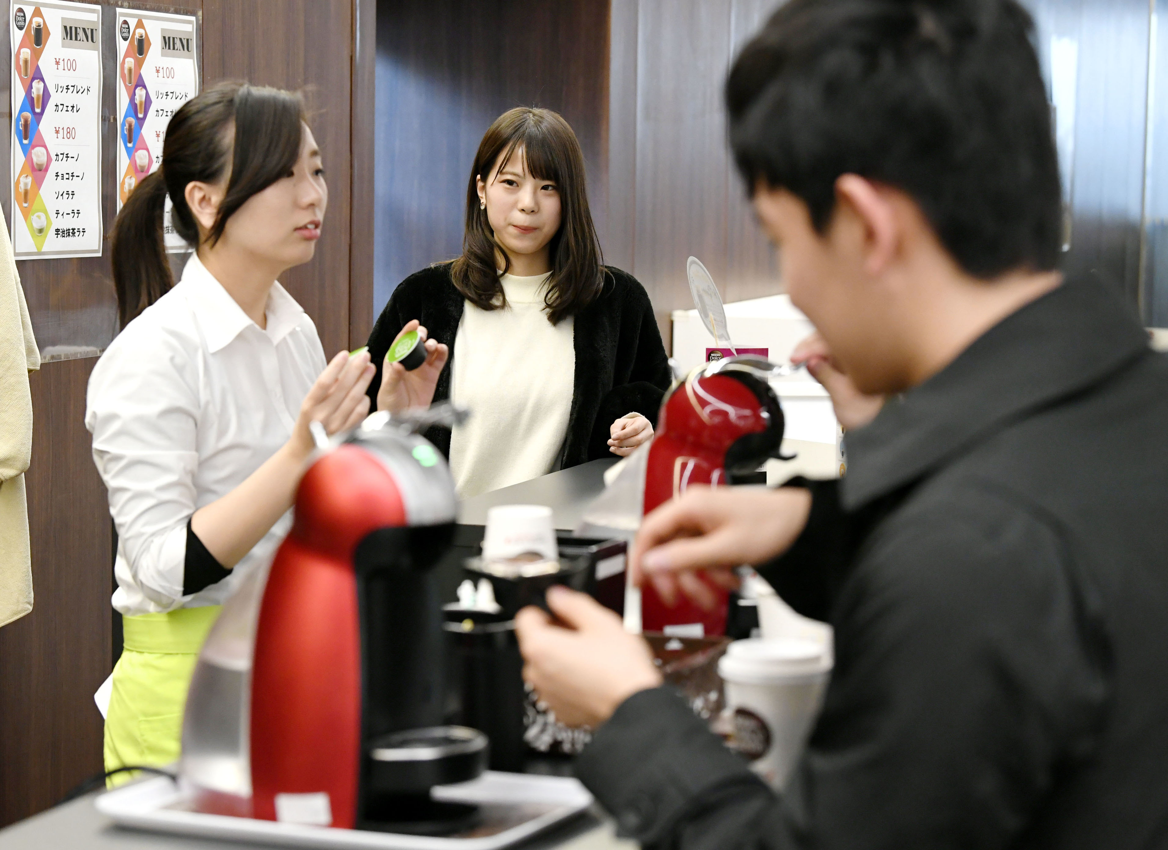 接客をする川島萌(左)と、その様子を見守る西牧友香=2017年12月、東京都世田谷区の産業能率大