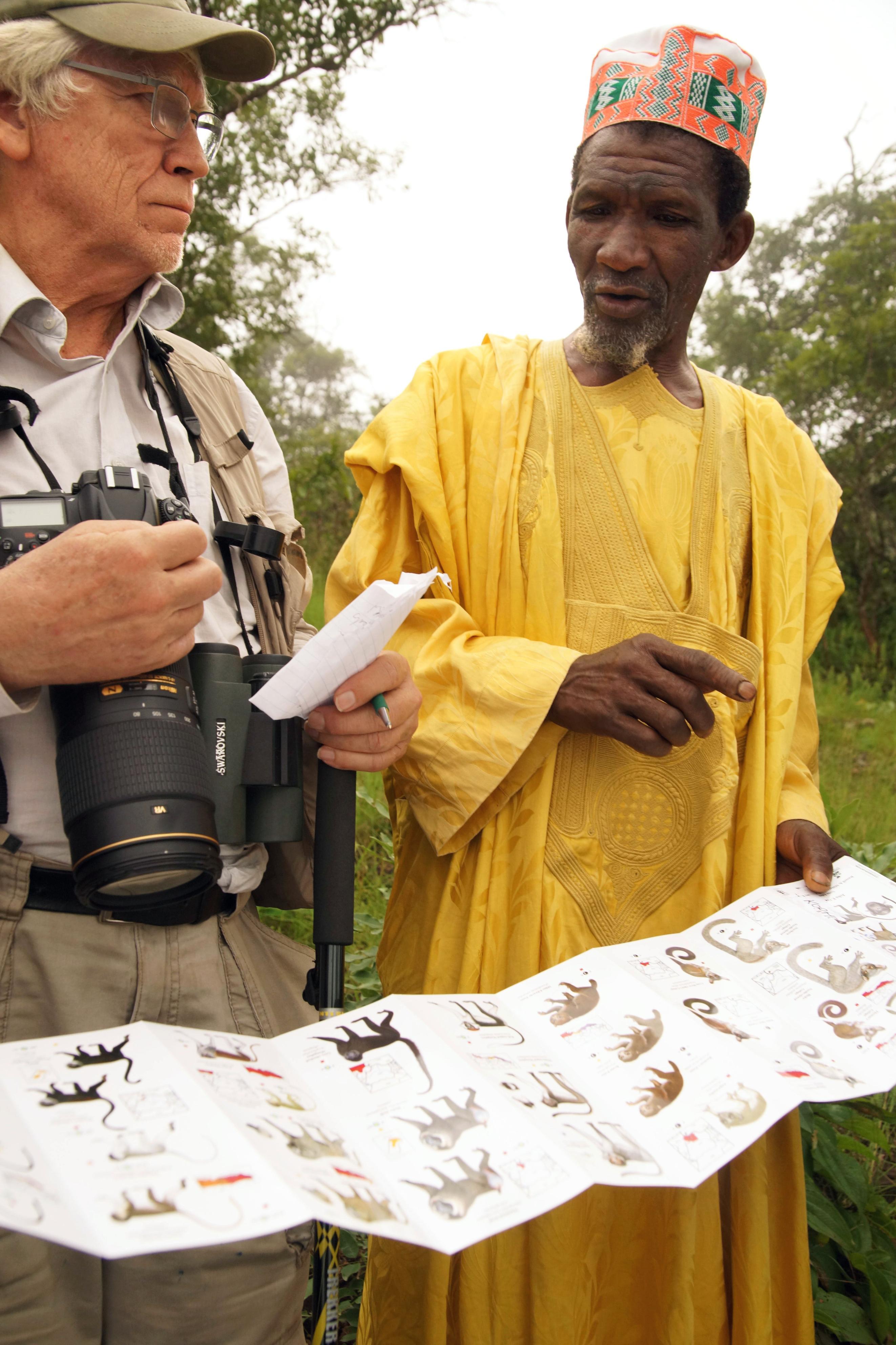 フィールドガイドを手に霊長類の様子を語るサリー・アマドゥ(右)。ミッターマイヤーが次々に質問を浴びせる=ギニア・ラベ近郊