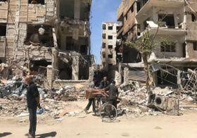 化学兵器が使われた疑いのあるシリア・ダマスカス近郊東グータ地区ドゥーマで、壊れた建物の前にたたずむ人々=16日(AP=共同)