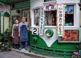 店の顔である路面電車の横に並ぶ安達征治さん(右)と妙子さん=長崎市東古川町