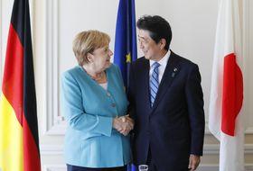 ドイツのメルケル首相と握手する安倍首相=24日、フランス南西部のビアリッツ(共同)