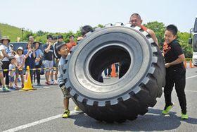 重さ300キロの巨大タイヤを持ち上げる子どもら=龍ケ崎市で