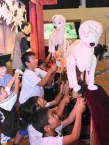 人形劇の鑑賞後、舞台裏で人形に触れる本城小児童ら