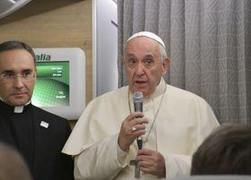 19日、ローマ法王特別機内で記者団にあいさつする法王フランシスコ(右)(共同)