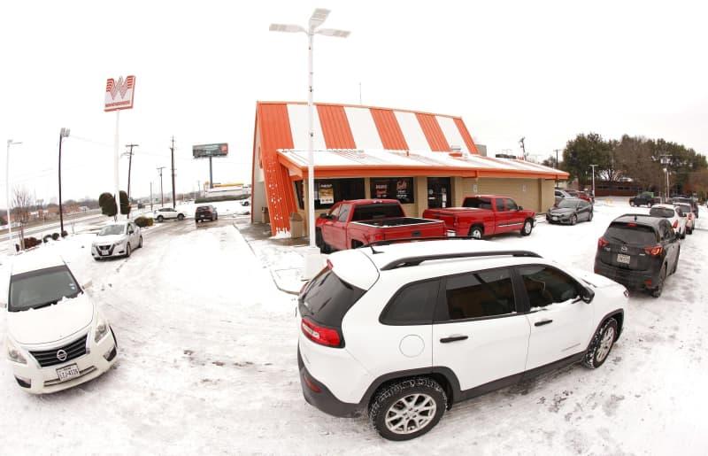 17日、寒波により多くのレストランが閉店する米テキサス州で、食事のためハンバーガー店に並ぶ車(ゲッティ=共同)