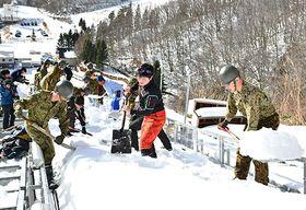 助走路の除雪に汗を流す自衛隊員や県スキー連盟の関係者=山形市蔵王ジャンプ台(クラレ蔵王シャンツェ)