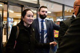 20日、カナダ西部バンクーバーの裁判所を出る華為技術の孟晩舟副会長(左)(ロイター=共同)