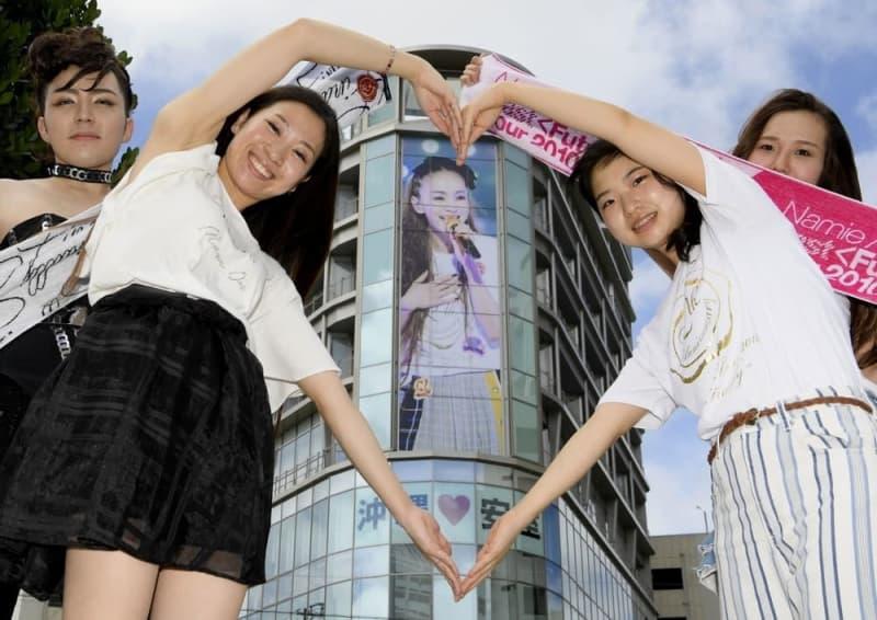 那覇市内のビルにある安室奈美恵さんの巨大写真をハートで囲うファン=2018年9月15日午前