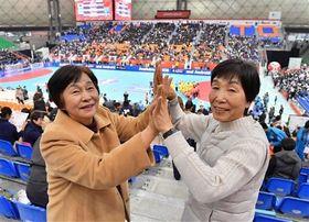 中国に勝利し、ハイタッチで喜ぶ元ハンドボール日本代表の竹内夏枝さん(左)と中川照美さん=6日午後、熊本市東区のパークドーム熊本(高見伸)