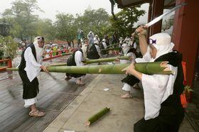 京都・鞍馬寺の「竹伐り会式」で、五穀豊穣を祈り大蛇に見立てた青竹をたたき切る僧兵姿の男たち=20日午後