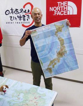 コース予定が書かれた日本地図を手に、プロジェクトについて説明する田中陽希さん=16日、東京都昭島市