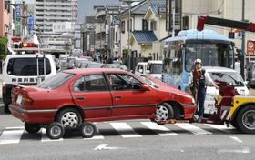 事故現場から運び出される乗用車=28日午後、神奈川県茅ケ崎市