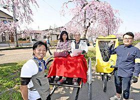 桜並木で人力車を走らせる大和田さん(左)とベロタクシーの江花さん(右)