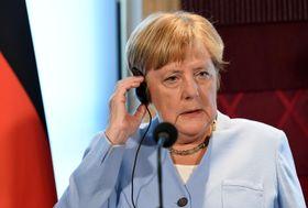 22日、オランダ・ハーグで記者会見するドイツのメルケル首相(ロイター=共同)