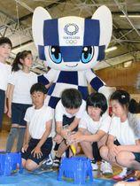 マスコットのミライトワとアサガオの種をまく児童ら=17日、神奈川県藤沢市