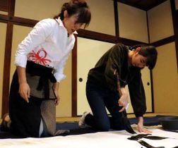 高田さん(左)の指導を受けながら書をしたためる酒見さん