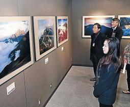 白山や立山連峰を収めた写真を眺める来場者=金沢市西泉2丁目のフジカラーギャラリーかなざわ