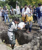 返還された遺骨が入った木箱を再埋葬する浦幌アイヌ協会のメンバーら=17日午後、北海道浦幌町